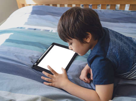New normal life, Kid using tablet for his homework, Child lying in bed  plying game on digital touch pad alone in bed room,Young boy lying down with mock up tablet.Home schooling, Social Distance, E-learning online education