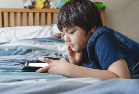 Kid using tablet for his homework, Child lying in bed playing game on digital touch pad in bed room,Young boy lying down with mock up tablet.Home schooling, Social Distance,E-learning online education