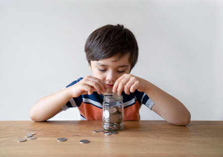 School Kid putting money sterling pound coins into clear jar, Child counting his saving money, young boy holding coin, Children learning about saving for future concept
