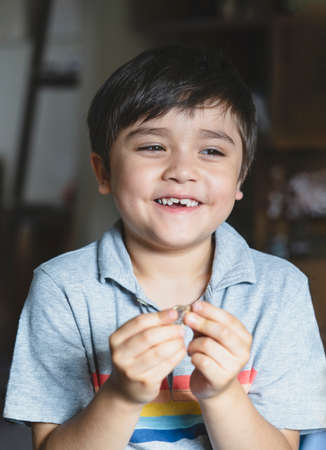 Portrait happy kid looking out with smiling face, Child playing alone  in living room, Candid shot cute young boy relaxing stay at home during covid lock down. Positive children concept,Social distancing