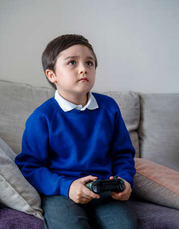 Portrait schoolkid holding video game or game console. Child playing game online at home after back from school, A boy relaxing at home