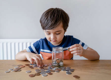 School Kid putting money coins into clear jar, Child counting his saving money, Young boy holding coin on his hands, Children learning about saving for future concept 版權商用圖片