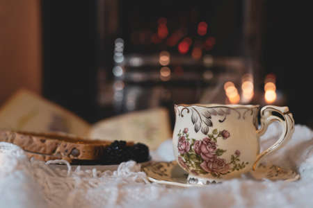 Hot coffee or cup of tea with steam and toast with blurry fireplace in drak room background, Scene cozy and relaxing for having breakfast in gloomy day on autumn or winter, English traditional