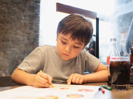 Portrait kid  drawing on white paper while waiting for food inrestuarant,Selective focus of kid enjoy colouring with yellow crayon on paper, Activity for children with family 版權商用圖片