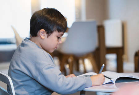 Portrait of school kid boy siting on table doing homework, Child holding pencil writing, A boy drawing on white paper on table, Elementary school and homeschooling concept Reklamní fotografie