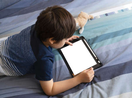Child lying in bed playing game on digital touch pad in bed room,Young boy lying down with mock up tablet.Home schooling, Social Distance,E-learning online education