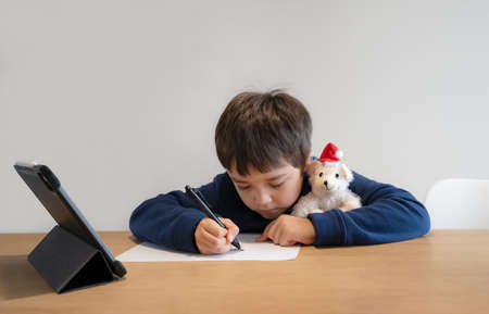 School Kid using pen drawing cartoon on paper, Child sitting alone doing home work, Young boy using digital pad searching information on internet for his study at home, E-learning online education