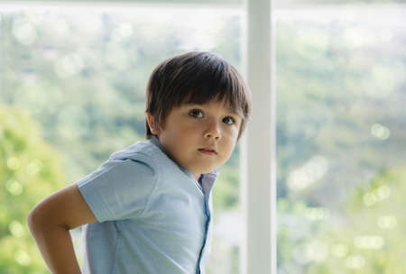High key light Portrait handsome kid standing next to window looking at camera with smiling face. Positive child boy relaxing on weekend in sunny day spring or summer Banco de Imagens