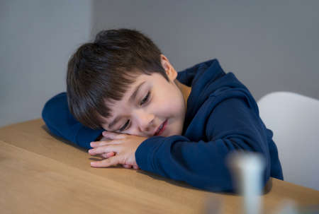 Portrait happy kid lying head down on his arm lookig out with smiling face, Day dream child laying head on table with little smile, Asianyoung  boy sitting alone, Positive children