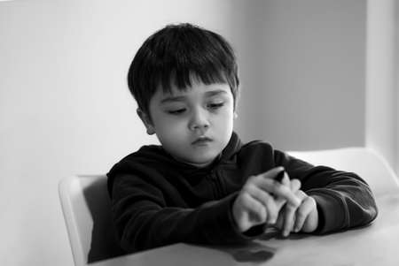 Black and white portrait Bored child siting alone table with unhappy face, Tired kid lookig down deep in throught, Lonely Young boy with sad face looking at his hands, Health metal concept