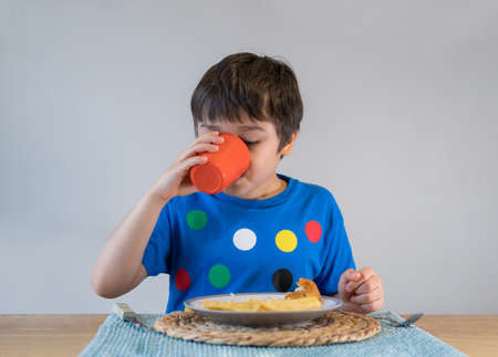 Young boy drinking water or orange juice, 7 year old kid boy having homemade fish and chips for Sunday dinner at home, Happy child eating lunch, Healthy life style concept