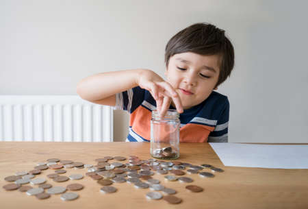 School Kid putting money coins into clear jar, Child counting his saving money, Young boy holding coin on his hands, Children learning about saving for future concept Stockfoto