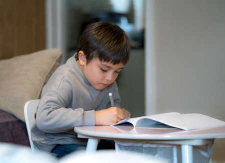 Portrait of school kid boy siting on table doing homework, Child holding pencil writing, A boy drawing on white paper on table, Elementary school and homeschooling concept Stockfoto