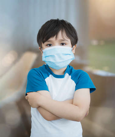 Covid-19, Social distancing with kid wearing medical face mask crosses hands and embraces own body looking at camera,Child boy hugging oneself wearing protective face mask for pollution pm2.5 or virus
