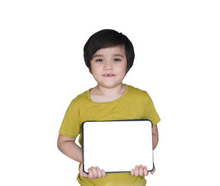 Isolated happy 6-7 year old kid with smiling face holding tablet on white background, New normal life, child boy using tablet learning at home, Home schooling,E-learning online education concept
