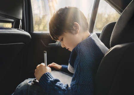 Happy young boy using a tablet computer while sitting in the back passenger seat of a car with a safety belt, Child boy drawing on smart pad,Portrait of toddler entertaining him self on a road trip.