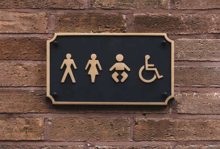 All gender restroom sign on wall in  Black  and Gold with letters and frame, WC - Toilets icon in public restroom sign with a male, female , kid and disabled symbol on brick wall