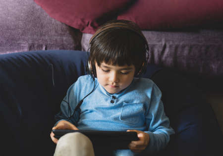 School kid wearing headphone listening the teacher teaching online class on tablet,Child boy studying and doing homework on digital pad,Home schooling,Distance education, e-learning online 版權商用圖片