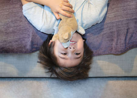 Active kid laying upside down watching TV on the sofa, Happy Child playing with dog toy, Cute boy is lying his backs on couch and making funny face, Children relaxing at home 版權商用圖片