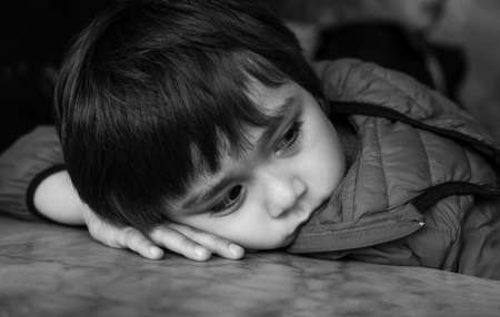 Black and white photo of Kid with bored face,Lonely boy putting his chin down on table and looking out deep in thought, Upset preschool child with unhappy or sad face, Spoiled children 版權商用圖片