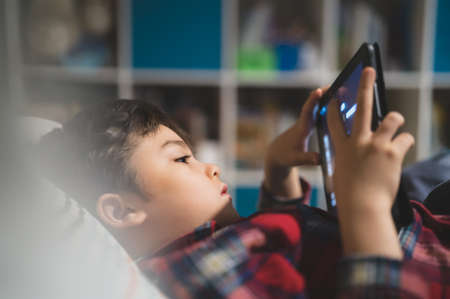 Soft focus young kid playing game alone on tablet, Cute boy watching cartoons on digital pad while lying in bed, Candid shot Happy child relaxing and enjoying on his own in bed room in the morning. 版權商用圖片