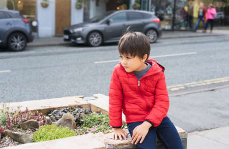 Lost Kid sitting alone next to a busy street in a center of city, Young boy with worrying face looking looking out deep in throught with blurry car on the road background,Lost children concept