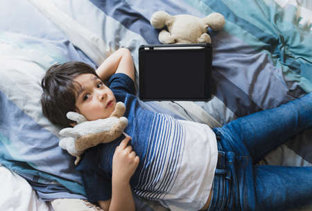 Kid laying in bed with dog toy and looking up at camera, Cute child boy lying in bed with tablet,Top view Children having activity on his own in bedroom with mock up of digital tablet.