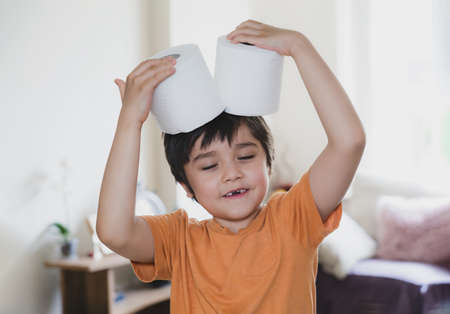 Happy young boy with smiling face playing with toilet paper, kid putting toilet roll on his head, Child holding two white tissue, Children health care concept 版權商用圖片