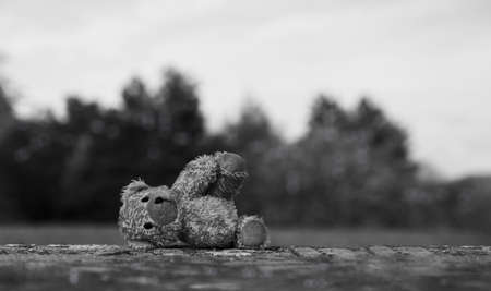 Lost Teddy bear with sad face lying on footpath with blurry background,Lonely bear doll laying down on the brick floor in gloomy day,lost toy or Loneliness concept, International missing children'day 版權商用圖片