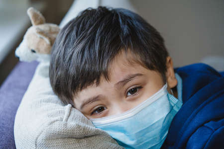 Close up face of Sick child wearing a protective mask, ill child in medical face mask lying head on sofa with sad face,Upset boy sitting on couch, Patient isolated in house to prevent infection. 版權商用圖片