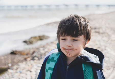 Portrait Kid with dirty mouth of chocolate ice cream with blurry sea view background,Candid shot happy child standing alone  with smiling face. A boy playing outdoor in sunny day the summer