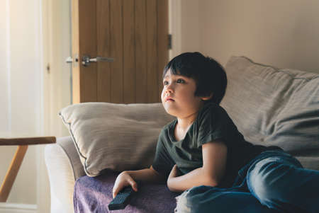 Cinematic Portrait of young boy lying on sofa watching TV in living room, Kid holding remote control, Child llies on couch looking up with surprised face. 版權商用圖片