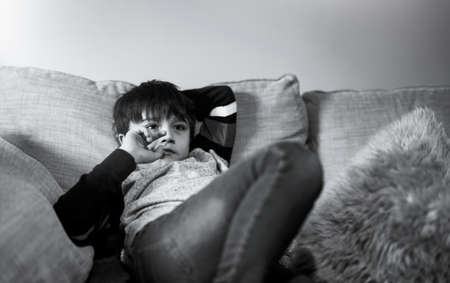 Kid putting finger in his mouth.Schoolboy biting his finger nails while watching TV, Cinematic portrait young boy siting on sofa looking out with thinking face or nervous, Children Health care