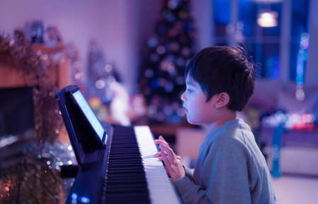 Cinematic night portrait of kid playing piano with neon lights, Young boy learning music with an electric piano in living room, Child relaxing sing a song at home in Christmas night 版權商用圖片