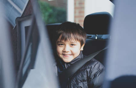 Cinematic portrait boy siting in safety car seat looking at camera with smiling face,Child sitting in the back passenger seat with a safety belt, School kid traveling to school by family car.Back to school 版權商用圖片