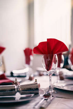 Empty glasses set with red napkin on dinning table with bright light shining through from window. Table set for Chritsmas party in dinning room with bokeh background in Cinematic tone. 版權商用圖片