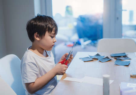 Kid using scissors cutting white paper , schoolboy making art and craft for his homework,Child learning how to use the scissors cut the paper,Children learn and play at home, Home school concept 版權商用圖片