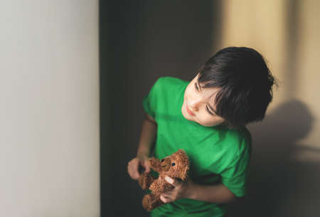 Kid playing hide and seek, Cute boy holding teddy bear hinding in the shade of the wall, Child having fun and relaxing at home on weekend, New normal lifestyle, Positive children concept 版權商用圖片