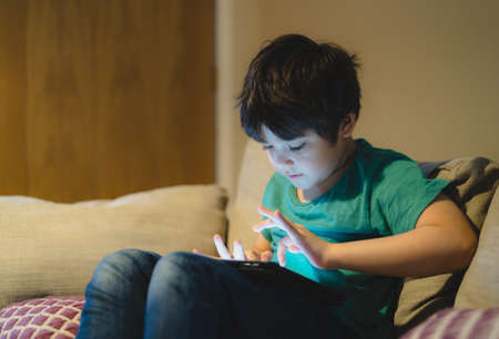 Cinematic portrait kid sitting on sofa watching cartoon on tablet, Cute boy playing game on touch pad, Child having fun and relaxing on his own in living room, New normal lifestyle