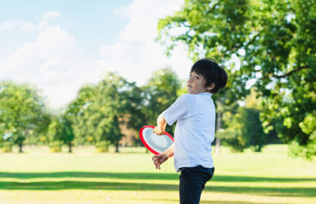 Happy kid playing in the park,Child having fun playing outside in sunny day spring,School boy have fun with flying disc in green field after school in summer,Sport and recreation  for children concept 版權商用圖片