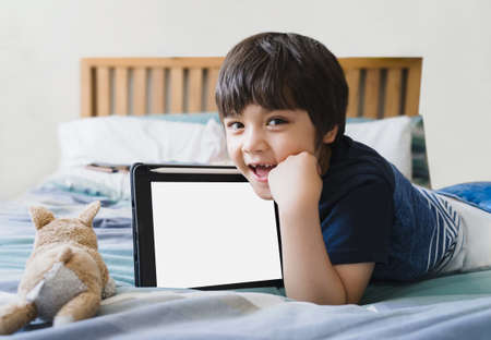 Kid laying in bed with dog toy and looking up at camera,Cute child boy lying in bed with tablet,Top view Children playing alone in bedroom with mock up of digital tablet.New normal lifestyle