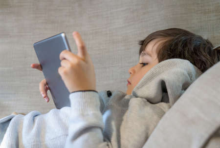 Cropped shot kid lying on sofa watching cartoons on tablet,6-7 year old boy playing game on touch pad, Cute Kid having fun and relaxing on his own in living room, New normal lifestyle