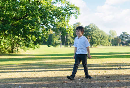 Portrait of happy school kid playing in the park, Child having fun playing outside in sunny day spring,  Little boy relaxing outdoor after school in summer. Positive children concept