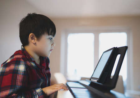 Portrait of kid playing piano, Young boy learning music with an electric piano in living room, Child relaxing sing a song befor bed.
