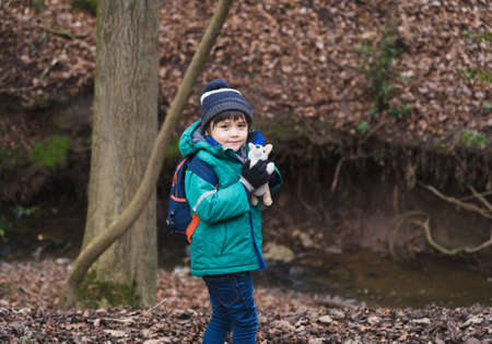Young boy playing with dog toy and looking at camera with smiling face, Kid explorer and learning about wild nature in countryside, School kid carrying backpack walking in Autumn or Winter forest