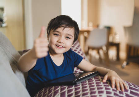 Kid with blurry thumb up,Selective focus Child sitting on sofa with smiling face.Boy stay at home using tablet learning online lesson from school,Home school,Distance education,E-learning concept