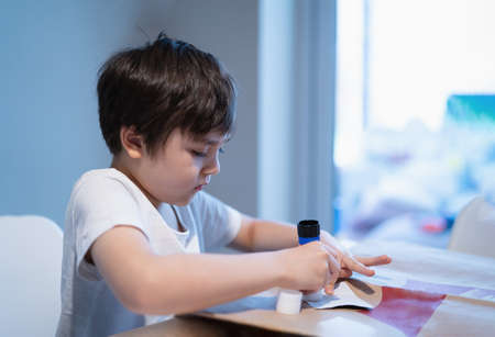 Preschool kid putting glue stick on paper for his school homework, Young boy using glue stick on paper making DIY project, Children learn and play at home, Home school