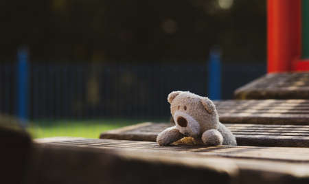 Lost teddy bear lying on wooden bridge at playground in gloomy day, Lonely and sad face brown bear doll lied down alone in the park, lost toy or Loneliness concept, International missing Children day 版權商用圖片