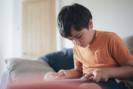 Portrait of school kid siting on table doing homework, Child boy holding pencil writing on paper, Homeschooling , back to school concept