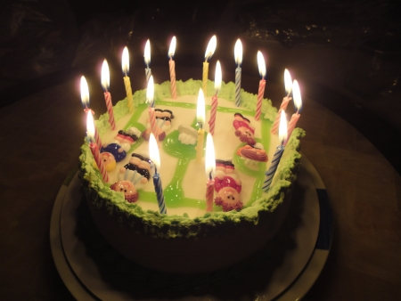 Birthday cake with football player doll in the dark photo